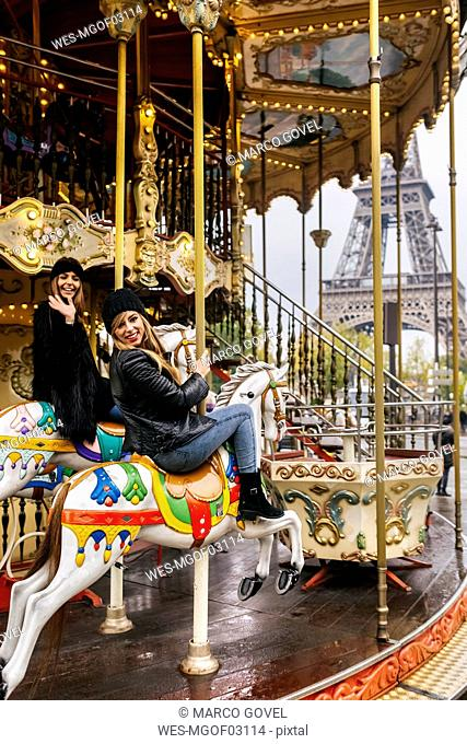 France, Paris, two best friends riding a carousel with the Eiffel Tower in the background