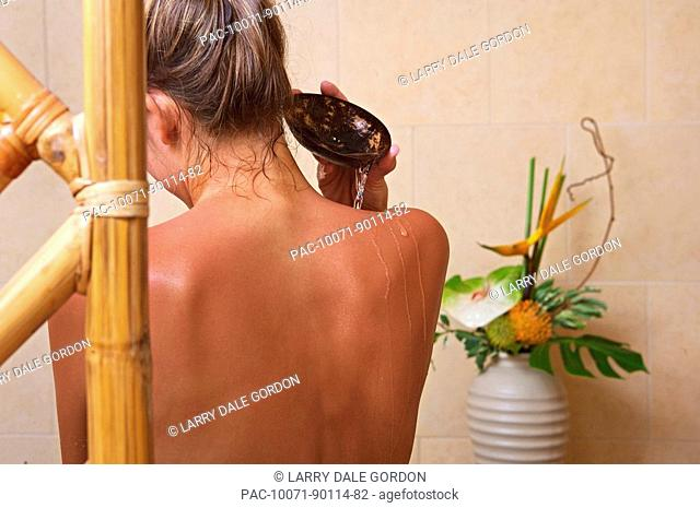 Hawaii, Oahu, Woman pours water down her bare back in spa setting, View from behind