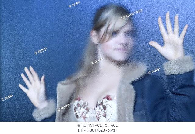 Young woman wearing jacket, standing behind frosted glass, close-up