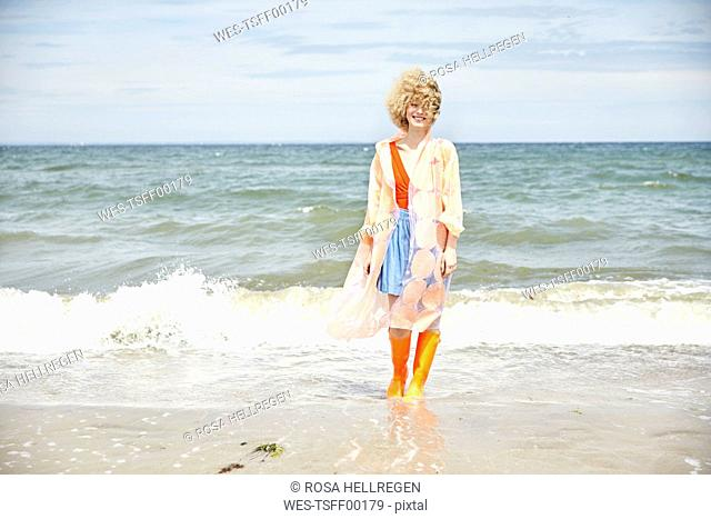 Smiling young woman wearing rain coat and Wellington boots standing at seaside