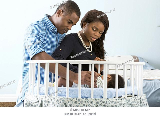 Couple admiring sleeping baby son in crib