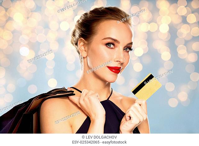 people, luxury, holidays and sale concept - beautiful woman with credit card and shopping bags over lights background