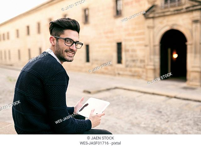Young mna using tablet on a city break