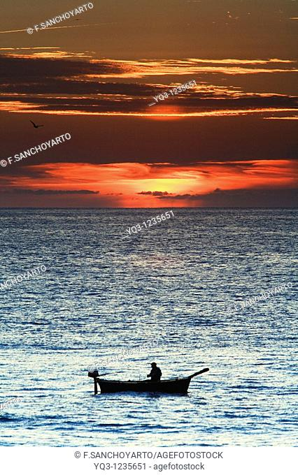 Fisherman in his boat at sunrise. Castro Urdiales, Cantabria, Spain