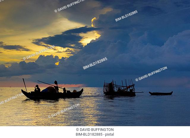 Silhouette of fishing boats floating in river