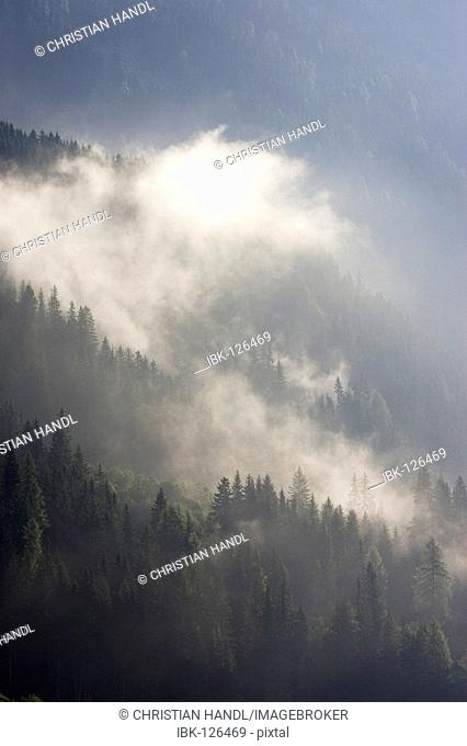 Morning fog on the mountains with are situated at the Antholzer lake South Tyrol Italy