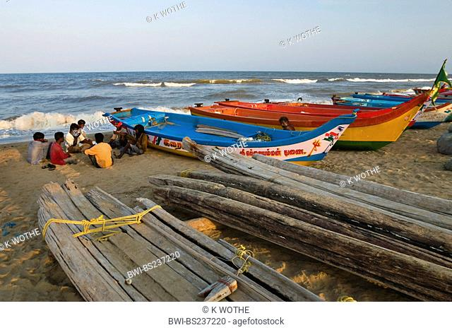 fishermen sitting on sand beach beside their boats, India, Tamil Nadu, Marina Beach, Chennai