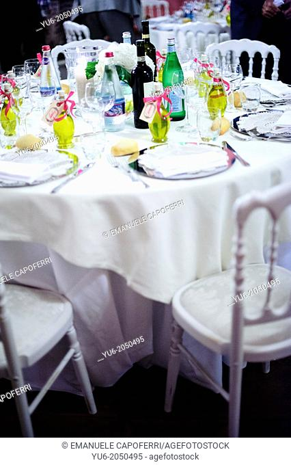 Table set for wedding dinner, with bottles of olive oil