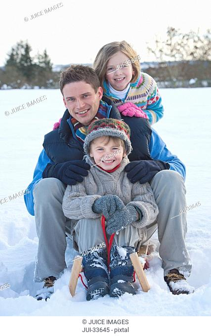Portrait of smiling family sitting on sled in snow