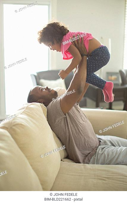 Father and daughter playing on sofa