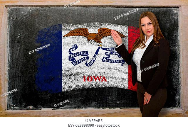 Successful, beautiful and confident woman showing flag of iowa on blackboard for marketing research, presentation and tourist advertising