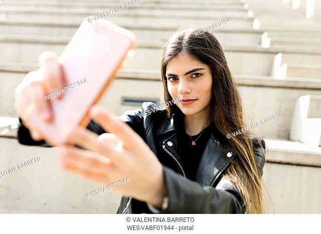 Portrait of young woman on stairs taking a selfie