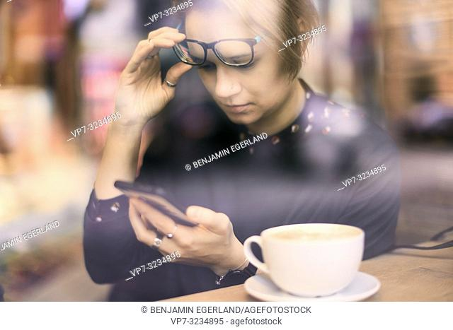 woman behind glass window touching glasses, using smartphone next to coffee cup in café in Munich, Germany
