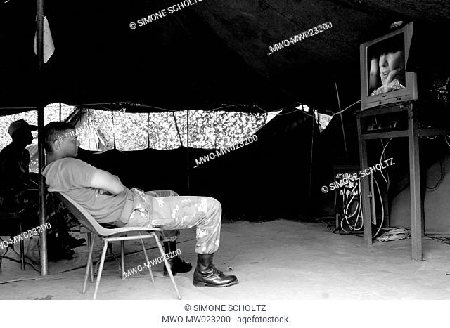 A member of the South African Defense Force, spending time in the television tent while he is off-duty, at the Kebezi military base, in Bujumbura Rural