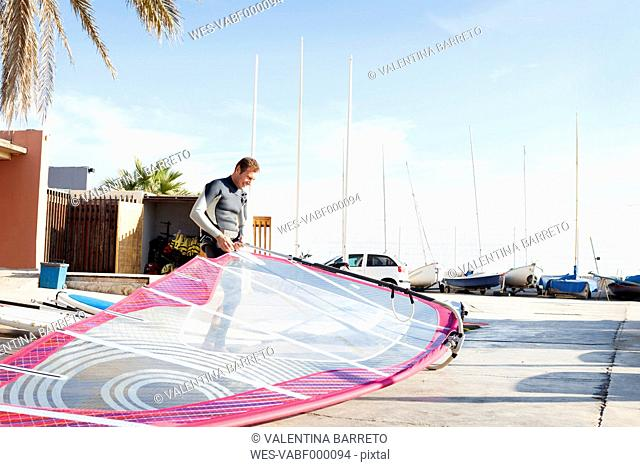 Man at car park holding surfboard