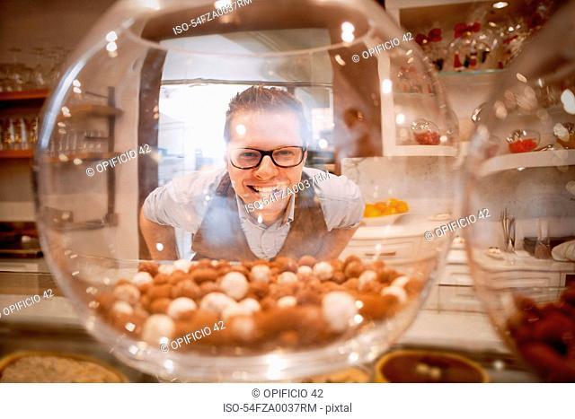 Cashier smiling behind glass bowl