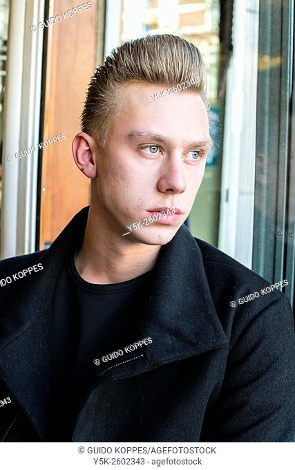 Rotterdam, Netherlands. Portrait young, blonde man just after recieving his new hairdue at Schorem Barbers and Haircutters