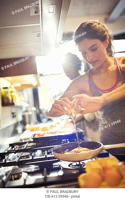 Young woman cracking egg over skillet on stove in kitchen