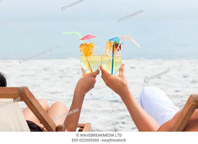 Couple clinking glasses of cocktail on beach