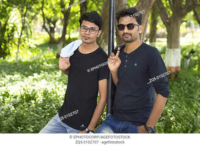 Two handsome young men in casual trendy clothes looking at camera