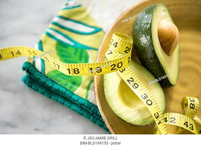 Close up of halved avocado, measuring tape and napkin on plate