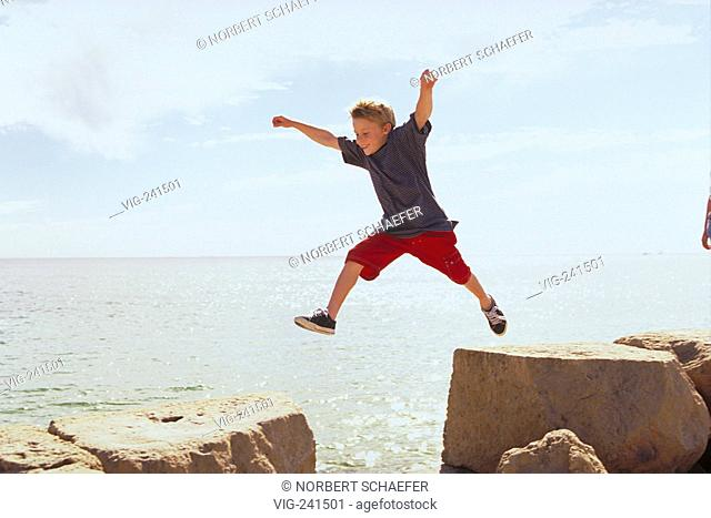beach-scene, portrait, full-figure, blond 13 years old boy wearing a black t-shirt, red shorts and sneakers jumps at a rocky coast from rock to rock  - GERMANY