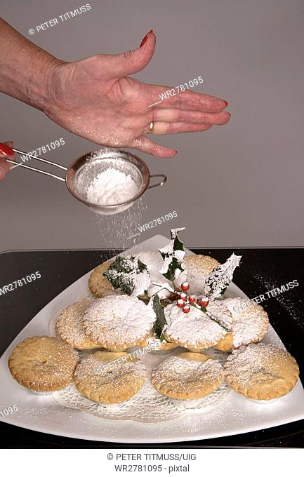 Traditional mince pies with a covering of icing sugar and a sprig of holly