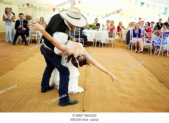 Bride and groom dancing together inside a marquee