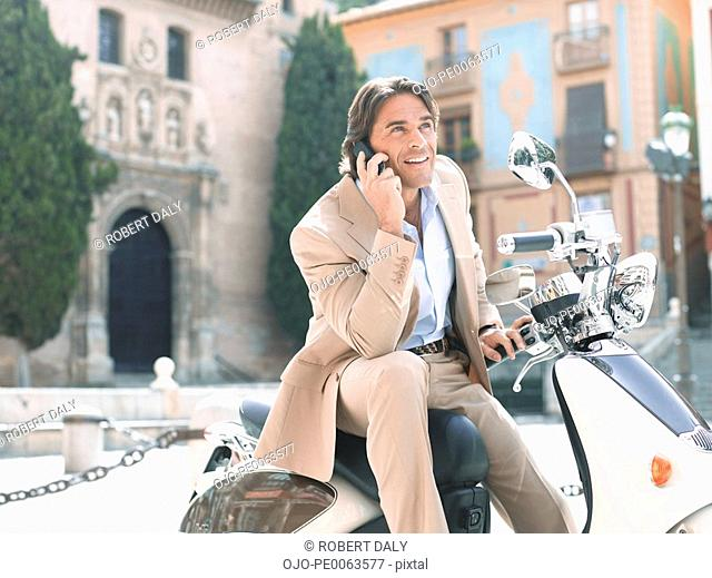 Businessman sitting on scooter and talking on cell phone