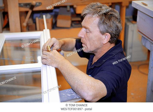 Germany, Upper Bavaria, Schaeftlarn, Carpenter fixing window door handle
