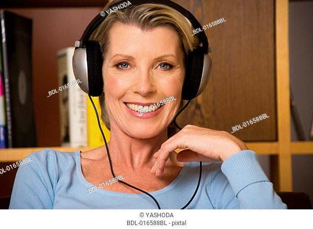 portrait of mature woman listening to music with headphones