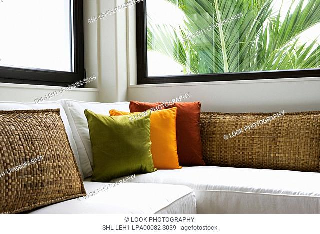 White corner sofa with brightly colored throw pillows