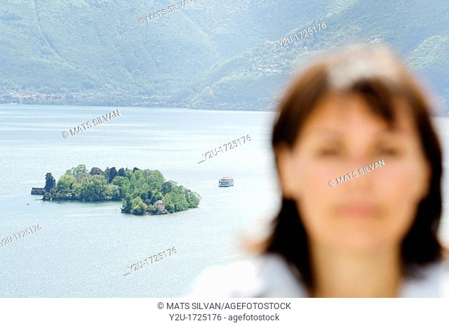 Close up on a woman and brissago islands in the background with a passenger ship