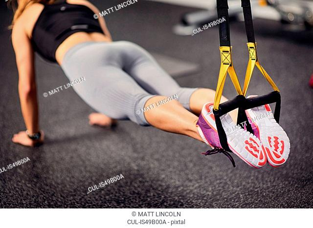 Neck down view of young woman doing push ups using exercise handles in gym