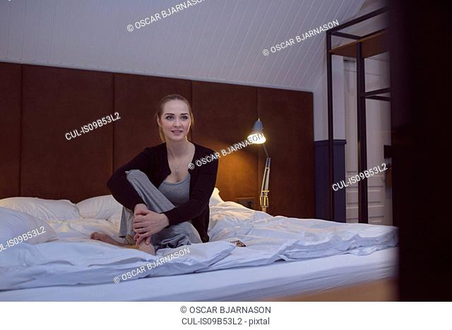 Young woman relaxing on bed, watching television
