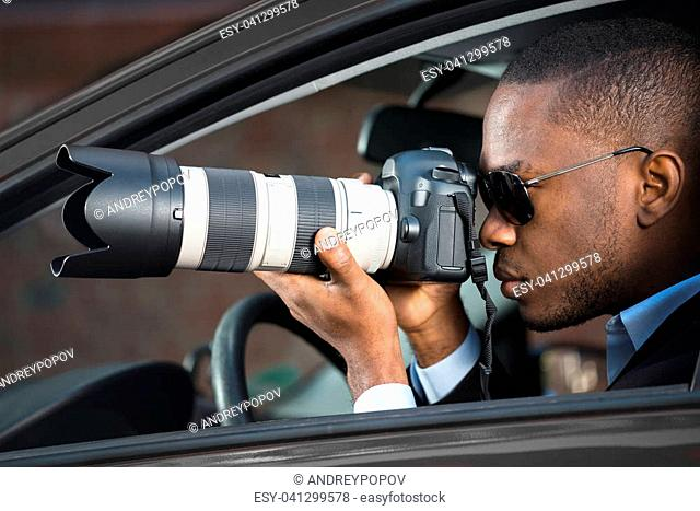 Private Detective Sitting Inside Car Photographing With SLR Camera