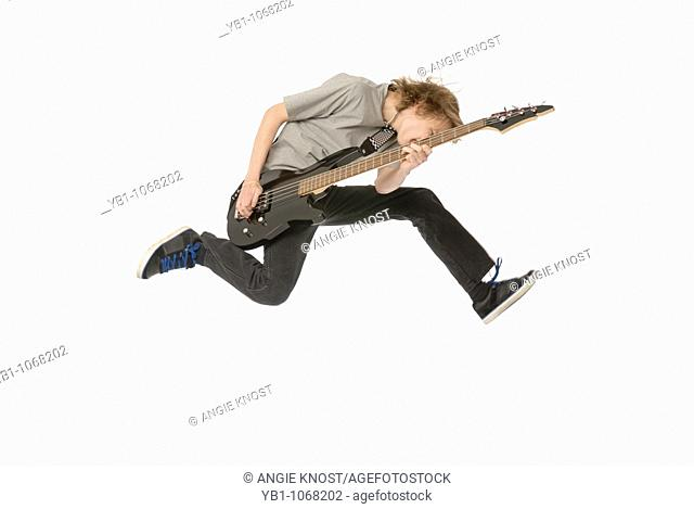 Teenage boy playing bass guitar while jumping in the air