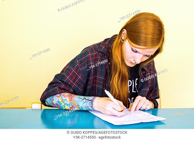 Tilburg, Netherlands. Young red haired female model signing a model release prior to a photo shoot
