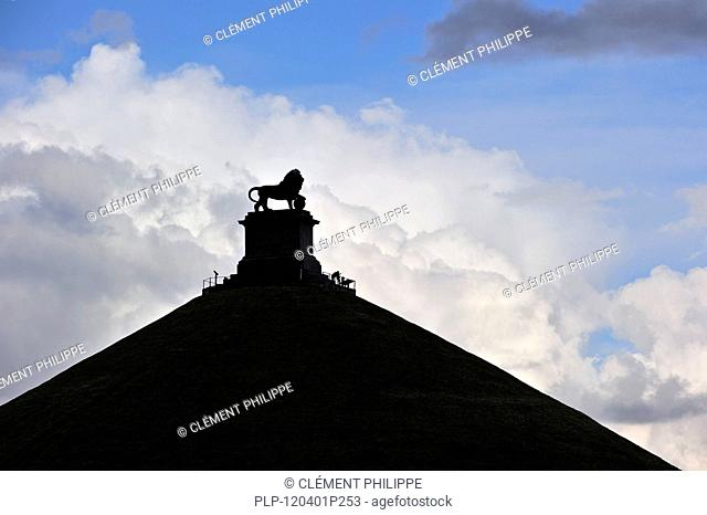 The Lion Hill silhouetted against cloudy sky, memorial monument of the 1815 Battle of Waterloo, Eigenbrakel, Belgium