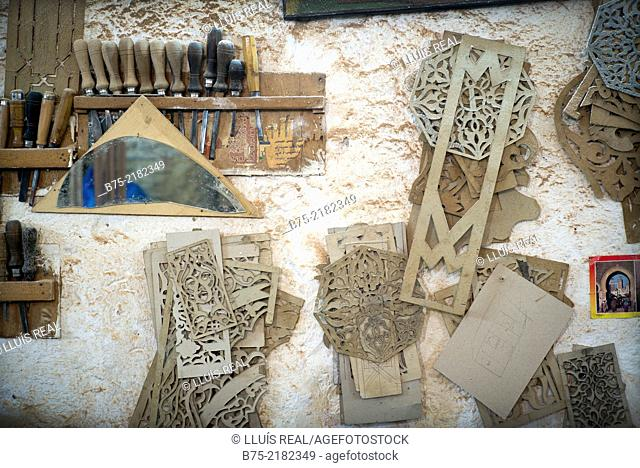 Closeup of arabesque designs templates and tools hanging on the wall of a cabinet-making in the Medina of Fez, Morocco, Africa