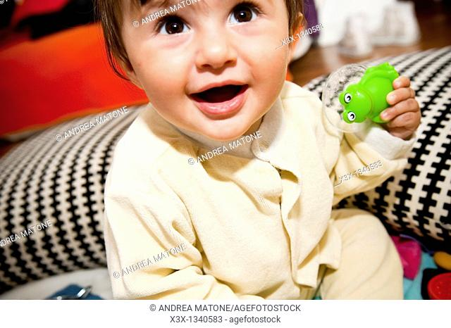 Baby girl holding a frog toy