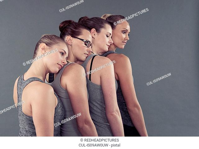 Young women in a row, leaning on each other, grey background