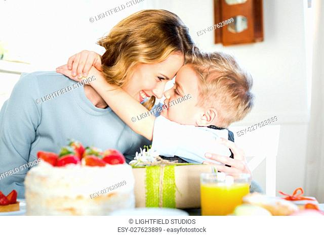 Happy mother and son hugging and touching foreheads while sitting at festive table