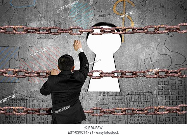 Businessman climbing on old iron chain for keyhole door with blank white view and business concept doodles wall background