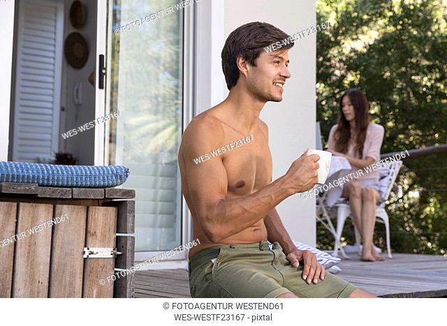 Man sitting on terrace with cup of coffee and woman in background