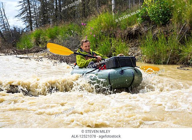 A man pack rafting on Jarvis Creek floats over a submerged log, Interior Alaska; Alaska, United States of America