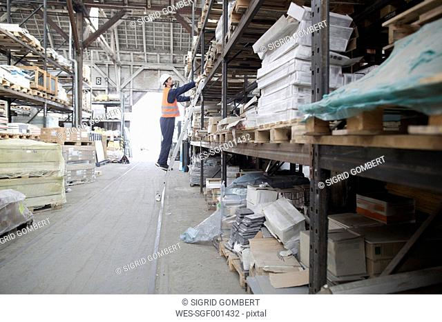 Warehouseman in storehouse at rack