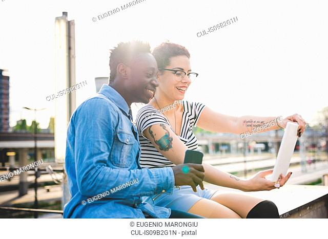 Couple looking at digital tablet smiling, Milan, Italy