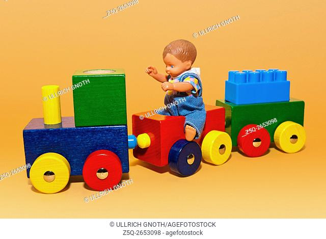 Wooden toy train with a doll boy riding on it