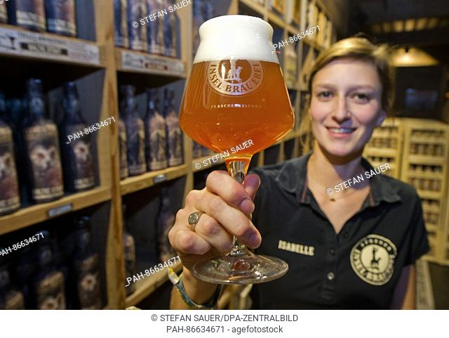 Isabelle Scharff, worker at the Insel-Brauerei (lt. island brewery) presenting a glass of 'Ueberseehopfen' beer in the warehouse sales room at the...